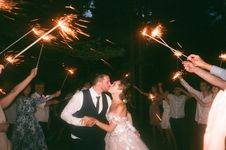 Free People Raising Lit Sparklers While Encircling Bride And Groom Kissing Stock Photos - 126192223