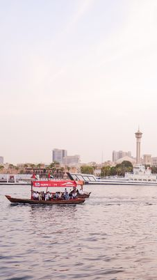 Free People On Red Boat Near Gray Pavement With View Of City Royalty Free Stock Image - 126192316