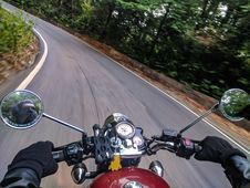 Free Person Driving Motorcycle On Curved Concrete Road Near Trees Stock Photo - 126192880