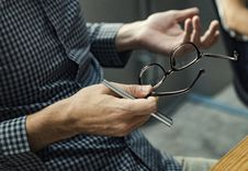 Free Person Holding Pen And Eyeglasses Royalty Free Stock Photos - 126192948