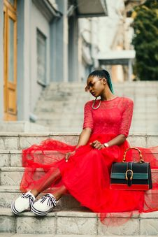 Free Woman Wearing Red Long-sleeved Dress Near Black Leather Bag Sitting On Concrete Stairs Posing For Photoshoot Stock Photography - 126193052