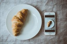 Free Croissant Bread On Round White Plate Beside Rose Gold Iphone Se Displaying Photo Of Croissant Bread On Plate Stock Photography - 126193452