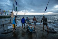 Free Four Person Pushing Boat Off Shore Royalty Free Stock Image - 126193656