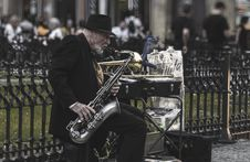 Free Man Sitting On Stool While Playing Saxophone Beside Fence Stock Photos - 126193753