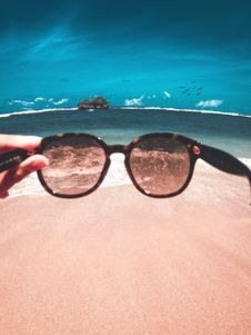 Free Person Holding Sunglasses In Front Of Beach Stock Photos - 126193793