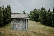 Free Brown Wooden Shed On Field With Green Trees Under Grey Sky Stock Images - 126194054