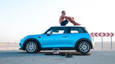 Free Man Sitting On Blue Mini Cooper Stock Photography - 126194402