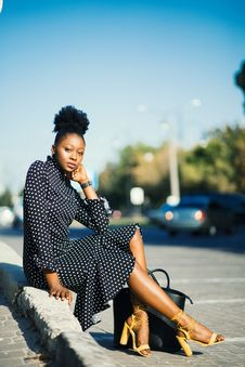 Free Woman In Black And White Polka-dot Dress Sitting Beside Pavement Stock Image - 126194411