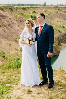 Free Groom And Bride Standing Near Green Grasses And River Stock Images - 126194524