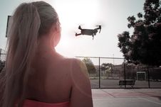 Free Woman Looking At Flying Drone Stock Photo - 126194870