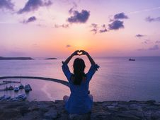 Free Woman Sitting On Rock Doing Heart Hand Gesture Stock Images - 126195104