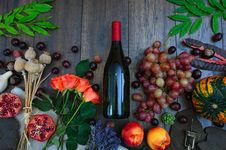 Free Wine Bottle Beside Grapes, Roses And Several Fruits On Brown Wooden Surface Stock Image - 126195341
