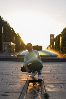 Free Man In White Sweatshirt Sitting In Front Of Water Fountain Stock Images - 126195854