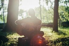 Free Man Siting On Grass While Playing Guitar Stock Image - 126195931