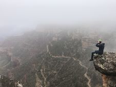 Free Man Sitting On Top Of Cliff On Foggy Mountain Stock Image - 126196041