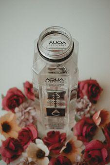 Free Aqua Bottle Surrounded By Flowers Stock Image - 126196351