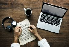 Free Person Writing Musical Notes Near Macbook, Cup Of Coffee, And Black And White Headphones On Table Royalty Free Stock Images - 126196419