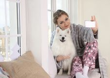 Free Woman Taking A Photo Of Herself With White Dog Stock Image - 126245391