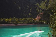 Free White Speed Boat On Body Of Water Across Green Trees Stock Photo - 126245600