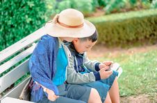 Free Boy Wears Gray, Blue, And Black Zip-up Jacket Holds Smartphone Next To Person Wears Beige Sun Hat Both Sits On Gray Wooden Bench Stock Images - 126245844