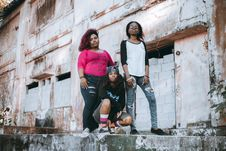 Free Three Woman Standing And Sitting On Concrete Ledge Stock Photos - 126246293