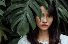 Free Woman Wearing White Shirt Standing Behind Leaves Of A Green Plant Royalty Free Stock Images - 126404529