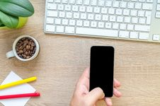 Free Person Holding Black Phone Near Apple Magic Keyboard On Brown Surface Royalty Free Stock Photography - 126652397