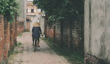Free Person Riding Bicycle In The Middle Of An Alley Stock Image - 126652501