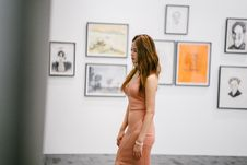 Free Woman Standing Near Paintings On Wall Stock Photography - 126652852