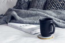 Free Black Ceramic Mug On Round White And Beige Coaster On White Textile Beside Book Royalty Free Stock Images - 126727609