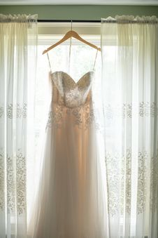 Free Hanged White Applique Corset Wedding Gown In Between White Window Curtain Inside Room Stock Photos - 126727763