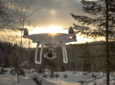 Free Photo Of White Drone Quadcopter Flying Near Trees At Noontime Stock Photo - 126808410