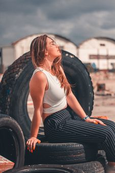 Free Woman Sitting On Vehicle Tires Stock Image - 126898361