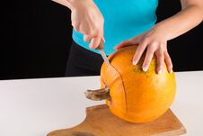 Free Girl Hand Cuts Big Orange Pumpkin On Wooden Board Royalty Free Stock Photography - 127058327