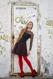 Free Woman Wearing Black And Red Long-sleeved Mini Dress And Red Leggings In Front Of A Closed White Metal Door Stock Photography - 127259972