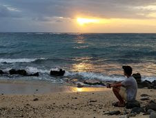 Free Man Sitting By The Beach Looking At Setting Sun Royalty Free Stock Photography - 127260297