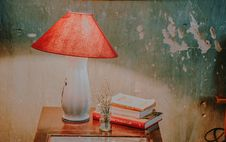 Free White And Red Table Lamp, Assorted-color Books, And White Petaled Flower In Clear Glass Vase On Brown Wooden End Table Royalty Free Stock Photography - 127260527