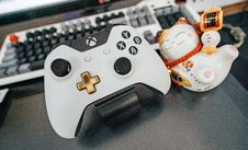 Free White And Black Xbox One Wireless Controller Beside White And Multicolored Ceramic Cat Figurine On Black Surface Royalty Free Stock Photography - 127260567
