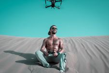 Free Man Sitting On Sand Controlling Drone Stock Images - 127260574
