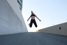 Free Woman Wearing Black Crop Top Jumping Beside The Building Stock Photo - 127327910
