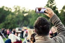Free Man Holding Phone Capturing Hot Air Balloon Stock Photos - 127450013