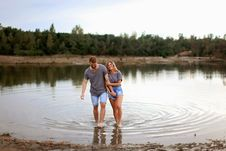 Free Couple Wearing Grey T-shirts Walking On Shallow Water And Smiling Royalty Free Stock Photography - 127450087