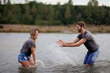 Free Man And Woman Playing On Body Of Water Stock Photos - 127450093