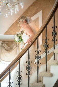 Free Woman Wearing Wedding Dress Holding Bouquet Walking Down Stairs Royalty Free Stock Images - 127650509