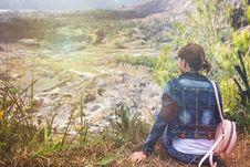Free Woman Wearing Blue Denim Jacket Sitting On Cliff Overlooking Open Field Stock Photo - 128037110