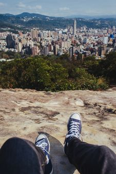 Free Person Sitting On Brown Rock Cliff While Overlooking On City Buildings Stock Image - 128037171