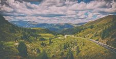 Free Road Surrounded By Green Pine Trees Across Hills Under Blue Cloudy Sky Stock Images - 128193824