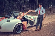 Free Man Helping Woman Stand From Car Stock Photography - 128405362