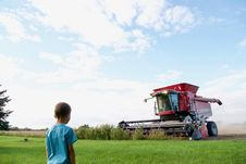 Free Boy Nears Red Harvester Machine Royalty Free Stock Photography - 128405487