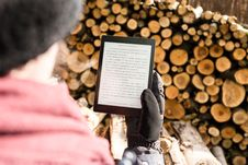 Free Person Holding Black E-book Reader Near Pile Of Firewood Stock Image - 128405651